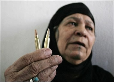 An elderly Iraqi woman shows